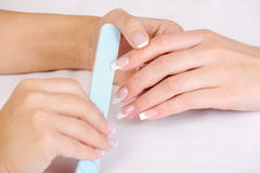 Manicurist   polishing female fingernails Stock Photos