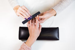 Manicurist polishing index finger for manicure Royalty Free Stock Images