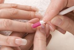 Manicurist preparing cuticles Royalty Free Stock Photo