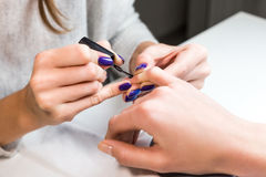 Manicurist put black shellac on the fingernails. Manicurist putting black shellac on the fingernails of a lady client in a beauty salon with a small applicator Stock Image