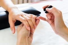 Manicurist putting cuticle softener Stock Photos