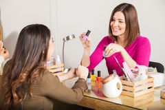 Manicurist recommending her favorite color. Beautiful young women working at a nail salon suggesting a nail polish color to one of her customers and smiling royalty free stock images