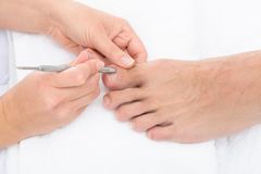 Manicurist removing cuticle from the nail. Close-up Of Manicurist Removing Cuticle From The Nails Of Feet royalty free stock photography