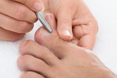 Manicurist removing cuticle from the nail Stock Images