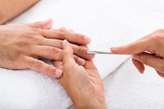 Manicurist Removing Cuticle From Person`s Nail. Close-up Of A Manicurist Removing Cuticle From Person`s Nail Stock Images