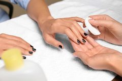 Manicurist removing polish from client`s nails in salon. Closeup stock image