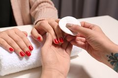 Manicurist removing polish from client`s nails in salon. Closeup stock photos