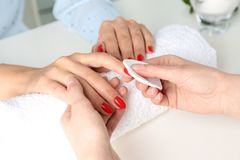 Manicurist removing polish from client`s nails in salon. Closeup royalty free stock photos