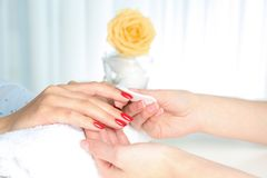 Manicurist removing polish from client`s nails in salon. Closeup stock images