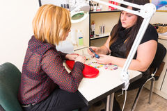 Manicurist Showing Client Blue Nail Polish Royalty Free Stock Photography