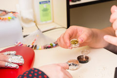 Manicurist Showing Gold Nail Glitter to Client Stock Photo