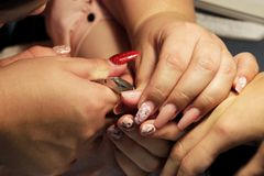 Manicurist at training courses shows students how to handle nails with the help of nippers cuticles before applying Stock Image
