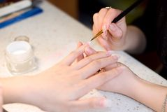 Manicurist treating client at beauty salon Royalty Free Stock Images