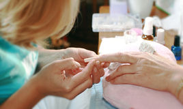 Manicurist treating customer. At beauty salon Stock Photos