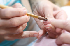 Manicurist treating customer. At beauty salon Royalty Free Stock Images