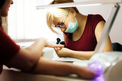 Manicurist working on client nails Stock Photos