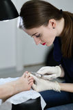 Manicurist working with forceps. And make a girl pedicure. Portrait profile of manicure in white gloves Stock Photos
