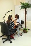 Manicuristen gör manicuren för kvinna i salong Royaltyfri Foto