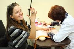 Manicuristen gör manicuren för kvinna by att spika polermedel Arkivfoton