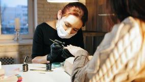 Manicuro de la mujer en la máscara médica que hace la manicura en salón de belleza almacen de video