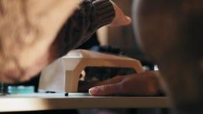 Manicuro de trabajo - secado de clavos en un equipo especial para la manicura profesional almacen de metraje de vídeo