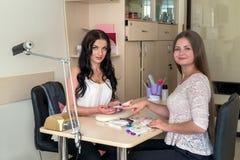 Manicurzysta i klient w piękno salonie z gwóźdź paletą fotografia stock