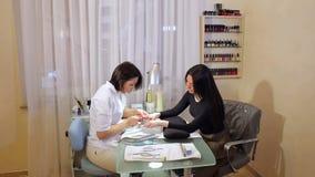 Manicurzysta robi manicure'owi dla m?odej kobiety opieka paznokcia gw??d? bawe?ny usun?? mopu lakier zbiory