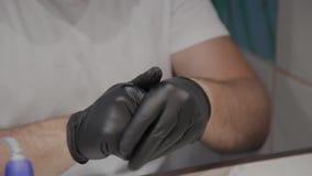 Manicurzysty mężczyzna dezynfekuje rękawiczki na rękach przed procedurą zdjęcie wideo