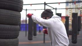 Manidrottsman nen i en utbildande maskering och boxastyper som boxas på gatautbildningsjordningen lager videofilmer
