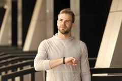 Manidrottsman nen på tillfredsställd framsida som kontrollerar tid, stads- bakgrund Idrottsman nen med borstet med den konditionb arkivfoto