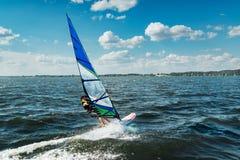 Manidrottsman nen rider vindsurfar över vågorna på sjön royaltyfri fotografi
