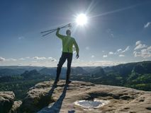 Manidrottsman nenlöpare med trekking poler som kör den steniga slingan royaltyfria foton