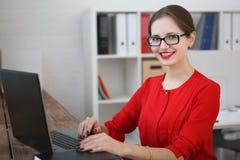 Manier bedrijfsvrouw in een rood overhemd en een glazenportret die, die in het bureau zitten en aan laptop werken Royalty-vrije Stock Foto