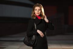 Manier blonde vrouw die in zwarte laag op de straat van de nachtstad lopen Royalty-vrije Stock Fotografie