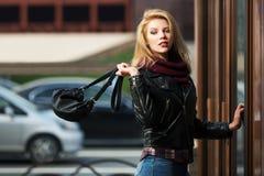 Manier blonde vrouw met handtas bij de wandelgalerijdeur Royalty-vrije Stock Fotografie