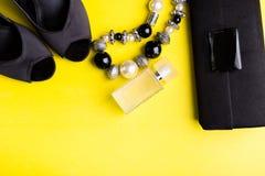 Manier Dame Accessories Set Zwarte en geel minimaal Zwarte Schoenen, armband, parfum en zak op gele achtergrond Vlak leg stock fotografie