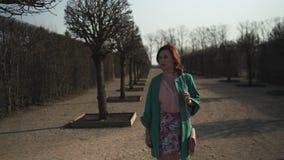 Manier die van het jonge vrouw lopen in een park in de Lente - Naakte bomen in Rundale-park houden - Gelukkig meisje in zonnig we stock video