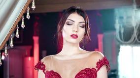 Manier donkerbruine vrouw met avondmake-up en rode lippen die bij luxeachtergrond stellen stock video