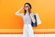 Manier elegant jong het glimlachen vrouwenmodel met het winkelen zakken die een zwarte hoeden witte broek over kleurrijke sinaasa Stock Foto