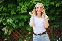 Manier gelukkig koel glimlachend meisje die op smartphone spreken royalty-vrije stock fotografie