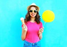 Manier gelukkige glimlachende vrouw met gele luchtballon en roomijskegel die strohoed dragen en roze t-shirt over kleurrijk blauw Stock Afbeelding