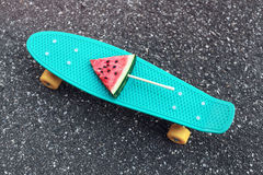 Manier groen skateboard met verse watermeloenijslolly op stok over geweven bestrating als achtergrond stock foto's