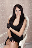 Manier het Mooie Donkerbruin Meisje Model stellen op luxestoel binnen Stock Foto's