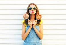 Manier jonge vrouw die lollys houden en haar lippen blazen Royalty-vrije Stock Foto's