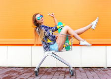 Manier koel meisje die pret in het winkelen karretjekar hebben met skateboard Royalty-vrije Stock Foto's