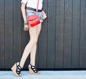 Manier langbenig meisje in mooie high-heeled schoenen in het korte de zomer van denimborrels stellen dichtbij de donkere muur Clo Royalty-vrije Stock Foto