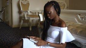 Manier modieuze Afrikaanse Amerikaanse modelzitting dichtbij de laag en het surfen van Internet stock footage