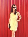Manier mooie donkerbruine vrouw die gele kleding en zonnebril met handtaskoppeling dragen in stad Stock Foto's
