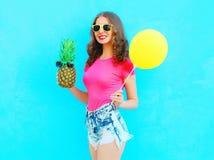 Manier mooie glimlachende vrouw met ananaszonnebril en gele luchtballon die een roze t-shirt over kleurrijk blauw dragen Stock Afbeeldingen