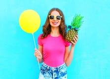 Manier mooie glimlachende vrouw met gele luchtballon en ananas die roze t-shirt over kleurrijke blauwe achtergrond dragen Stock Foto's
